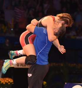 Helen Maroulis, who did not allow a point in winning her first World Championship, jumped into the arms of her coach Valentin Kalika. (Ginger Robinson photo)