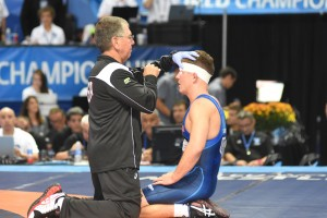 Bryce Saddoris (right) was examined by an official after he was head butted by his repechage opponent. Saddoris lost this bout and was eventually hospitalized after it was learned the 145.5 pounder fractured his left orbital. (Ginger Robinson photo)